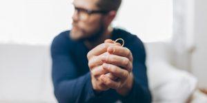 Heartbroken man holding a wedding ring